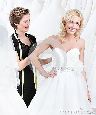 Free Seamstress Adjusts The Dress Of The Bride Stock Photography - 25918972