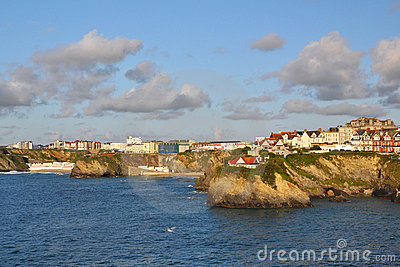 Seascape: sunset lit town on cliffs, blue skies