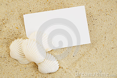 Seashell and card on sand