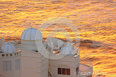 Oceanfront building at golden sea by dawn