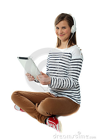 Seated girl enjoying music on portable device