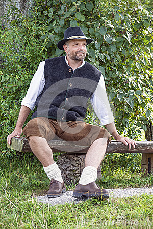 Seated man in traditional Bavarian costumes and black hat