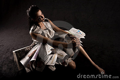 Seated woman with newspapers