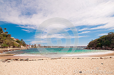 Secluded beach with green water and blue sky