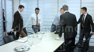 Secretary comes in a meeting room. Secretary comes in a meeting room a group of businessmen. Meeting managers