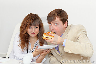 Secretary is feeding his boss at workplace
