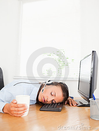 Secretary with headset sleeps in office