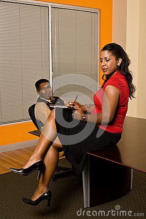 Secretary taking notes while business man stares