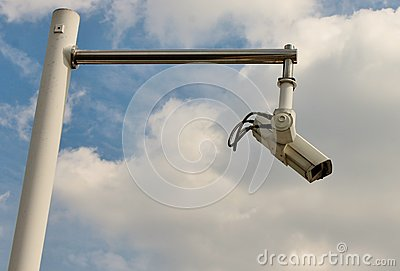Security camera on pole against sky