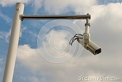 Security camera on pole against sky