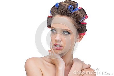 Seductive lady in hair rollers posing and looking away