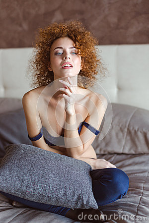 Seductive Tender Female With Curly Red Hair Sitting On Bed Stock Photo - Image: 64035454