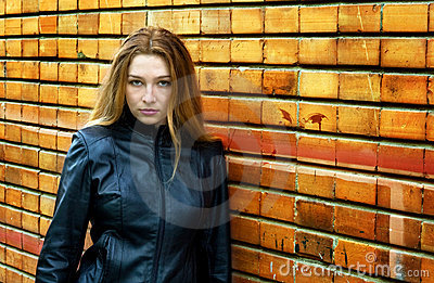Seductive woman in front of brick wall