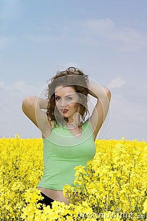 Seductive young woman in rape flower field