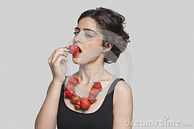 Seductive young woman wearing strawberry necklace as she eats one piece over gray background