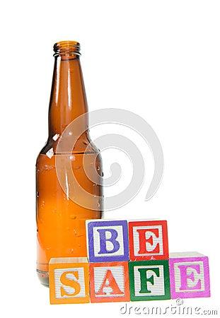 Segni i blocchi con lettere che compitano per essere sicuro con una bottiglia di birra
