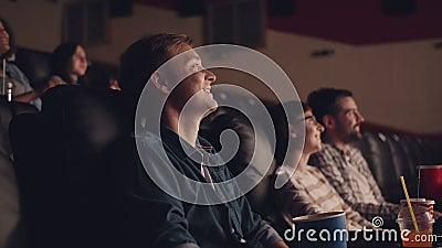 Seitenansicht junger Mann schauen Film im Kino essen pocorn lachen stock footage