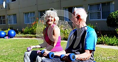 Seitenansicht von den kaukasischen älteren Paaren, die mit Dummköpfen im Garten des Pflegeheims 4k trainieren stock footage