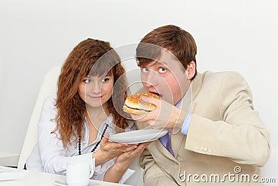 Sekretär speist seinen Chef am Arbeitsplatz