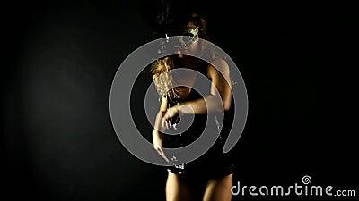 Seksowna blondynki kobieta z błyszczeć czerń wierzchołek i masque tana w zmroku zbiory