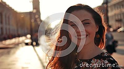Seksowna dziewczyna z długim czerwonym włosianym kręceniem wokoło i ono uśmiecha się na kamerze plenerowej zdjęcie wideo
