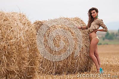 Seksowna młoda dziewczyna z słomianą belą