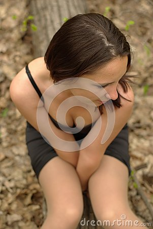 Self-conscious girl sitting in the forest