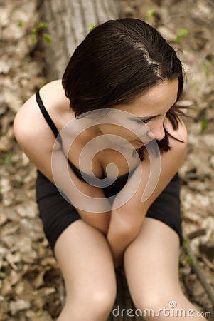 Self-conscious girl sitting on a log