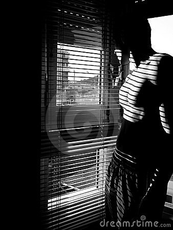 Self portrait of male model shirtless and looking out a window