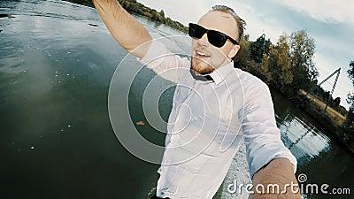 Selfie em câmera de ação de um empresário extremo em óculos de sol vagueia em um lago vídeos de arquivo