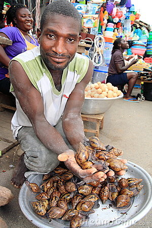 Seller of giant snails on African market