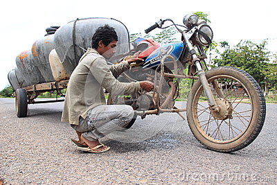 Selling water barrels from a motorbike in Cambodia Editorial Stock Photo