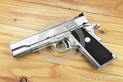 Semi-automatic handgun on grey wooden background, .45 pistol. Stock Photo