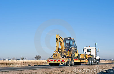 Semi-truck hauling a back-hoe loader combination