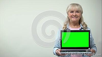 Senhora envelhecida que mostra o portátil com tela verde, molde de compra em linha dos descontos filme