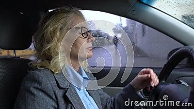 Senhora envelhecida Tired do negócio que senta-se no carro, exaustão grande da cidade, esforço do engarrafamento video estoque