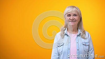 Senhora idosa alegre que olha à câmera e que sorri, cliente feliz com serviço filme
