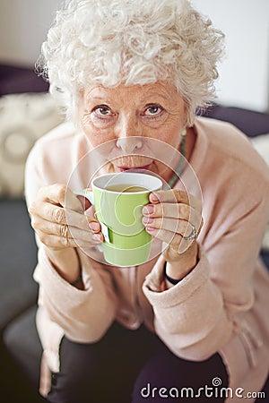 Senhora madura em casa que bebe o chá