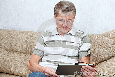 Senior adult man interested with tablet computer