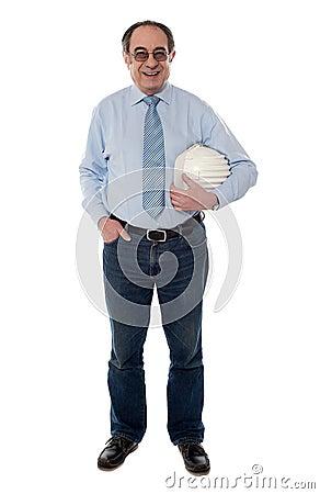 Senior architect holding hard-hat, full length