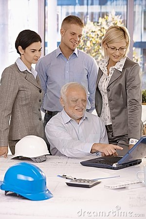 Senior architect showing work to team on laptop