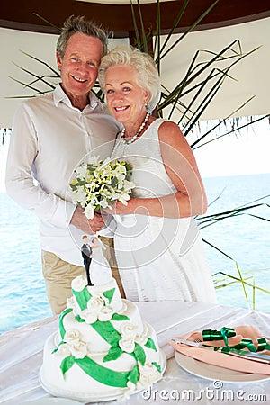 Senior Beach Wedding Ceremony With Cake In Foreground