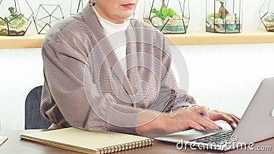 Senior Business Ladys schreibt in ihrem Notebook-Job stock footage