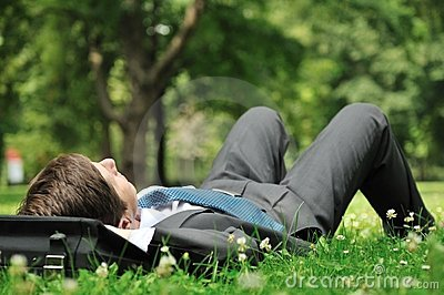 Senior business man lying in grass
