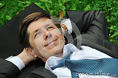 Senior business man lying in grass