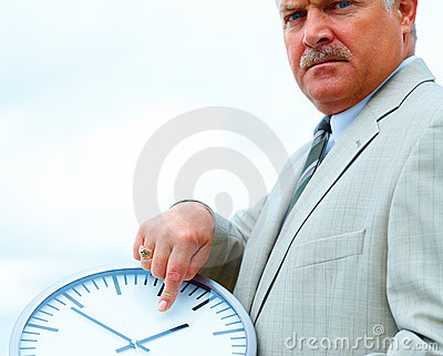 Senior business man pointing towards a clock