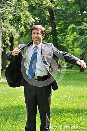 Senior business man putting on jacket