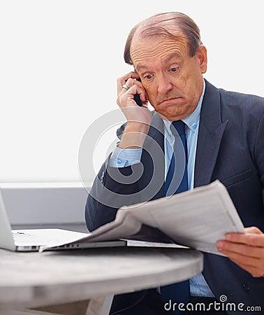 Senior business man reading newspaper on the phone