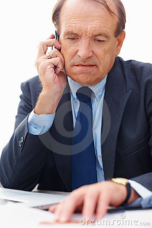 Senior business man reading newspaper on the phone