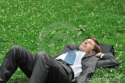 Senior business man relaxing in grass
